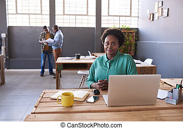 Confident African businesswoman using a laptop in a modern office