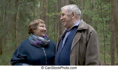 A beautiful old couple is walking in the park. Gently hold...