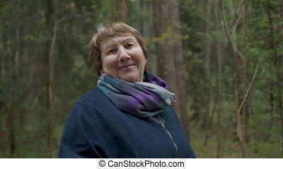 Portrait of an elderly beautiful woman. Walking in the park,...