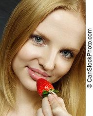 Young woman tasting strawberry - Young beautiful woman...