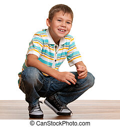 Squatting kid - A handsome smiling blond kid in casual...