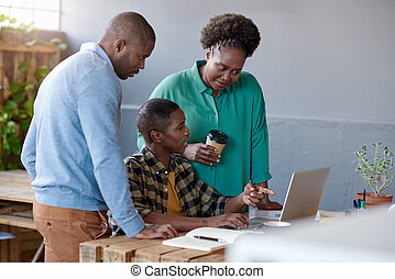 African businesspeople at work on a laptop in an office -...