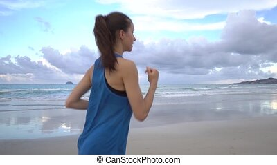 Healthy active young woman running along shore line at sunrise. Female jogging