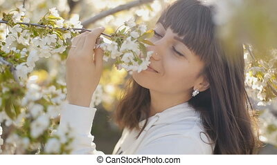 Woman smelling white flowers in springtime - beautiful woman...