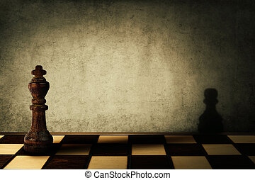 king complex - King chess piece casting a shadow of a pawn...