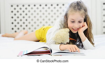 Little girl reading book with her plush friend.