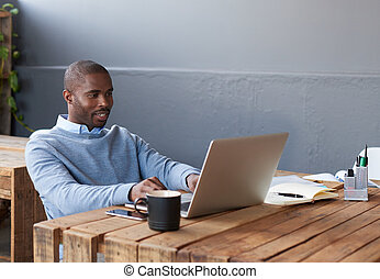 Smiling African businessman working on a laptop at his desk...
