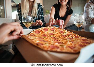 Group of friends eating big pizza and drinking - Cropped...