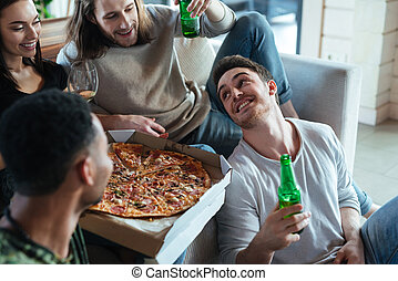 Cropped image of four friends sitting with pizza - Cropped...