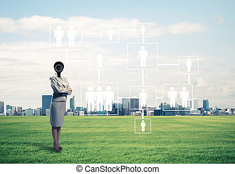 Camera headed woman standing on green grass against modern...