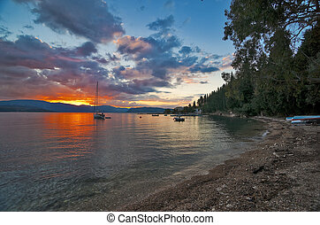 Sunrise in Corfu island and one of pebble beach near...