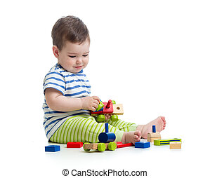 Baby boy playing with blocks toys. Isolated on white.