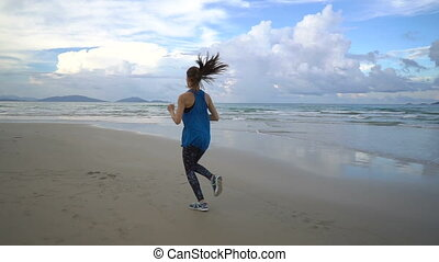 Young attractive woman jogging on the beach at sunset Full length. Beautiful clouds, sunset. Steadicam slow motion video.