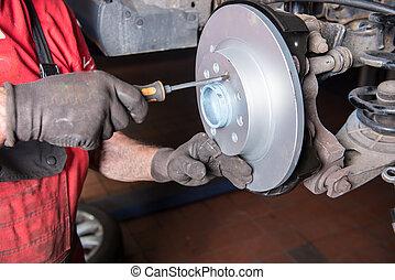 Assembler mounts new brake disc in a car repair