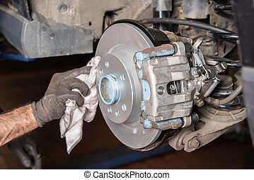 Assembler cleans a brake disc after installation in the car...