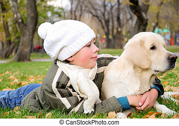 Boy playing in autumn park with a golden retriever