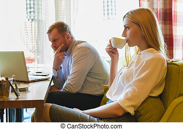 Business meeting in a cafe. Woman drinks coffee and man...
