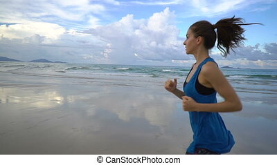 Sporty woman runner jogging on beach against blue sky. Fit young female in sportswear is running by idyllic sea. Runner is exercising in nature on sunny day.