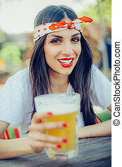 Beautiful happy woman holding a pint of beer and toasting....