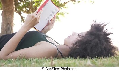 Young woman reading book in the park and sleep