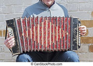 man playing concertina - man playing with an old grunge...