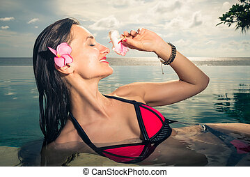 Female Tourist in infinity pool of hotel resort - Woman...