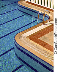 Swimming pool with stair at hotel close-up.
