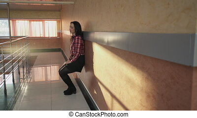 woman in office standing next to wall, sitting down in hall....
