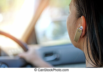 Women using hands-free phone while driving. - Women using...
