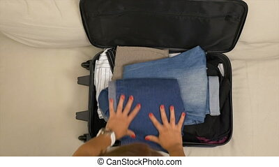 Woman packing clothes standing on her knees on overfilled...