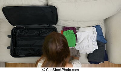 Young female traveler rushing to put clothes into travel bag...