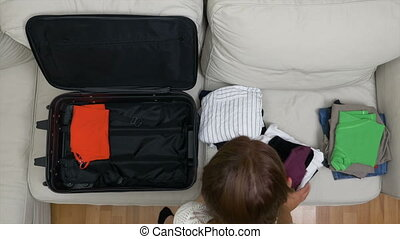Top view of business woman packing luggage in rush preparing...