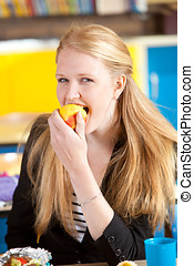 Eating a healthy apple - Blond schoolgirl eating an apple
