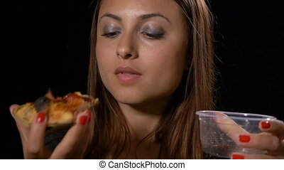 Woman looking satisfied eating delicious pizza and drinking...
