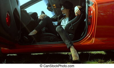 stylish lady on high heels posing in red sport car - Sexual...