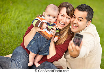 Happy Mixed Race Parents and Baby Boy Taking Self Portraits...