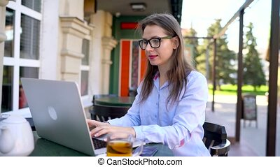 Beautiful young woman working in a cafe outdoors - modern...