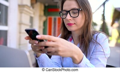 Beautiful young woman using smartphone in a cafe outdoors