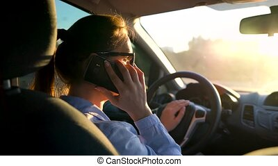 Woman in glasses speaks by smartphone in the car