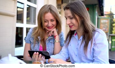 Two cheerful women talk and use a smartphone in a cafe - Two...