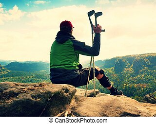 Tired man tourist  sit with  hurt knee in immobilizer or rock, hold  medicine pole.  Open forest landscape
