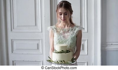 Beauty bride in bridal gown with cake and lace veil indoors....