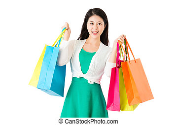 young woman of chinese holding bags showing shopping on the...