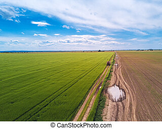 Tractor on country road through wheat field, drone pov