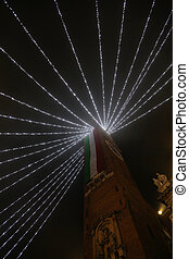 High bell tower with huge Italian flag with Christmas lights...