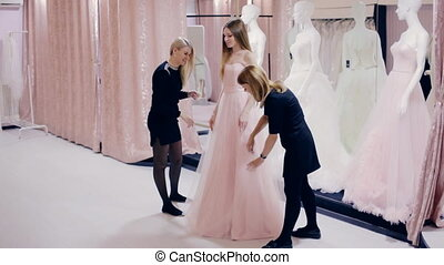 Pretty girl chooses a prom gown in boutique - girl chooses a...