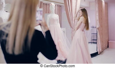 girl chooses a prom dress in shop - young woman chooses a...