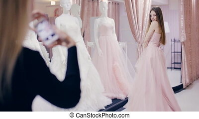 Pretty girl trying on wedding dress in fitting room - Pretty...