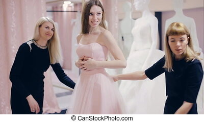 Pretty girl trying on prom gown in boutique - girl chooses a...