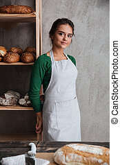 Happy young lady baker standing at bakery near bread. -...